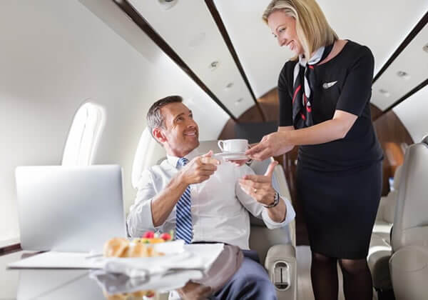 Female flight attendant serving passenger coffee on private jet