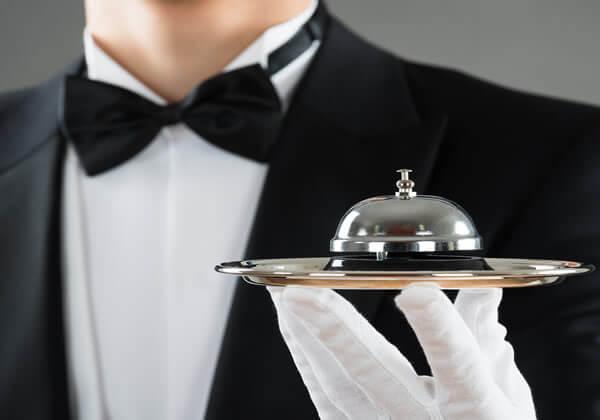 White butler in tuxedo holding silver bell